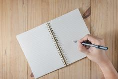 Hand of man use pencil writing on white notebook on wooden table Royalty Free Stock Photos