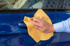 The hand of man wipes a car a yellow rag stock photos