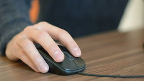 Hand of a man working at computer clicking on mouse