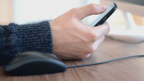 Hand of a man working at computer clicking on mouse and using smartphone. On table stock footage
