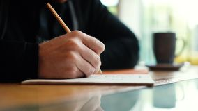 Hand of man writes text by pen on paper close-up in slow motion. There`s a cup on the table. Guy sits at a table in a cozy cafe next to a window stock footage