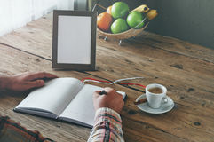 Hand of man writing in a blank notebook. On the wooden table. Next on the table is cup of coffee and an empty photo frame. Top view. Copy space. Free space for Royalty Free Stock Photography