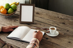 Hand of man writing in a blank notebook. On the wooden table. Next on the table is an empty frame. Top view. Copy space. Free space for text Stock Photos