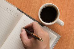 Hand of man writing in open notebook. On wooden table with hot coffee Royalty Free Stock Image