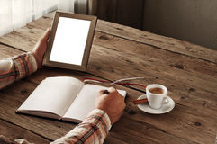 Hand of man writing something in a blank notebook. Other hand man holding an empty picture frame on wooden table. The concept of the memory of something. Top Stock Photo