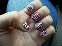 Hand with manicure in British Flag stile. Woman`s hands with blue manicure. stock photo