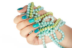 Hand with manicured nails holding colored necklaces Royalty Free Stock Image