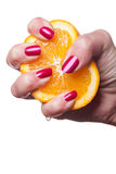 Hand with manicured nails touch an orange on white Stock Photo