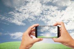 Hand manliga asiatiska hållande Smartphone som tar bilden av härligt n fotografering för bildbyråer