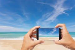 Hand manliga asiatiska hållande Smartphone som tar bilden av landskap V arkivbild