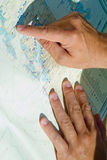 Hand and map. Hand pointing to a place on a marine map Stock Photography