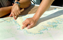 Hand and map. Hand pointing to a place on a marine map Royalty Free Stock Image
