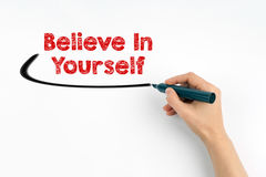 Hand with marker writing - Believe In Yourself concept. White paper background Stock Image