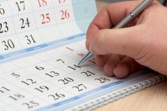Hand markiert Datum im Kalender lizenzfreie stockbilder