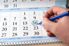 Hand markiert Datum am Kalender im Blau Lizenzfreie Stockfotos