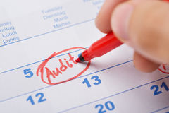 Hand Marking Audit On Calendar. Cropped image of hand marking Audit date on calendar Royalty Free Stock Photography