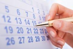 Hand marking date 15 on calendar. Closeup of woman's hand marking date 15 on calendar Stock Images