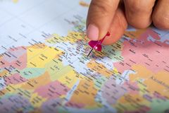Hand marking Greece on map with pin. Hand marking Greece on map with red pin stock photo