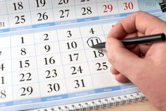 Hand marks date on the calendar in black Royalty Free Stock Image