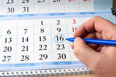 Hand marks date on the calendar in blue Stock Photos