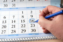 Hand marks date on  calendar in blue Royalty Free Stock Photos