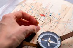 Hand marks places on the map with pins. royalty free stock images