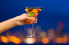 Hand with martini in front of city skyline bokeh Royalty Free Stock Image