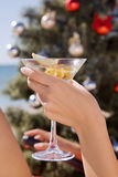 Hand with a martini glass in Christmas. On the beach near the Christmas tree Royalty Free Stock Image