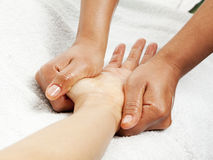 Hand massage. Massage therapist gently kneading female hand Stock Photo