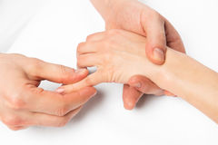 Hand massage, the masseur is working on every finger, close up Stock Photography