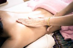 Hand massaging oil massage on to a woman back. In spa royalty free stock photos