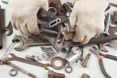 Hand of master in gloves with wrench to tighten the nut. Hand of master in gloves with a wrench to tighten the nut Stock Images
