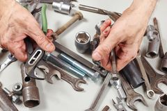 Hand of master with tools for repairing machines in workshop Stock Images