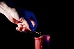 Hand with a match lights a red candle Royalty Free Stock Photography