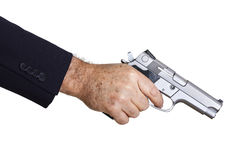 Aiming Diagonally Down. The hand of a mature adult man wearing a suit, holding a 9mm gun with his right hand, aiming it diagonally downwards Royalty Free Stock Photos