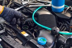 Hand of Mechanic check water in car radiator and add water antIfreeze coolant fluid to car radiator at garage , service and. Maintenance concept . selective royalty free stock photo