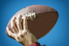 Hand med amerikansk fotboll Arkivbild