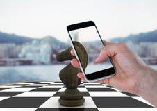 Hand med apparaten mot schackstycke och oskarp horisont Arkivfoton