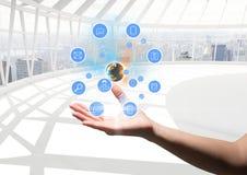 hand med applikationsymboler och jord över futuristic kontor Royaltyfria Bilder