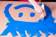 Hand med borstemålarfärger med blå målarfärg arkivfoton