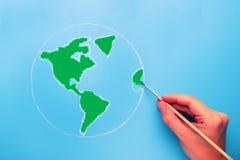 Hand med borstemålningvärldskartan i grön färg Arkivfoto
