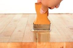 Hand med borsten som applicerar på den wood tabellen arkivbilder