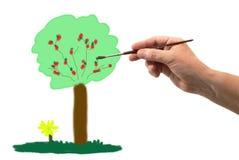 Hand med borsteteckningen ett träd arkivfoto