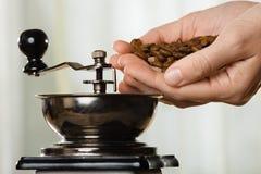 Hand med den kaffebönor och molar Royaltyfri Fotografi