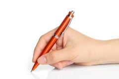Hand med den orange pennan Arkivfoto