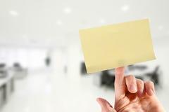 Hand med den tomma klibbiga anmärkningen på fingret i kontoret Royaltyfri Fotografi