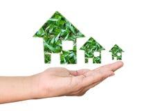 Hand med det isolerade gröna huset royaltyfria foton