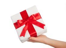 Hand med en gåva med ett isolerat rött band Arkivbild