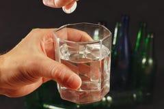 Hand med en löslig minnestavla från bakrus över ett exponeringsglas av vatten på mörk bakgrund Royaltyfria Foton