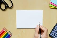 Hand med en penna och brevpapper på ett skrivbord Royaltyfri Foto